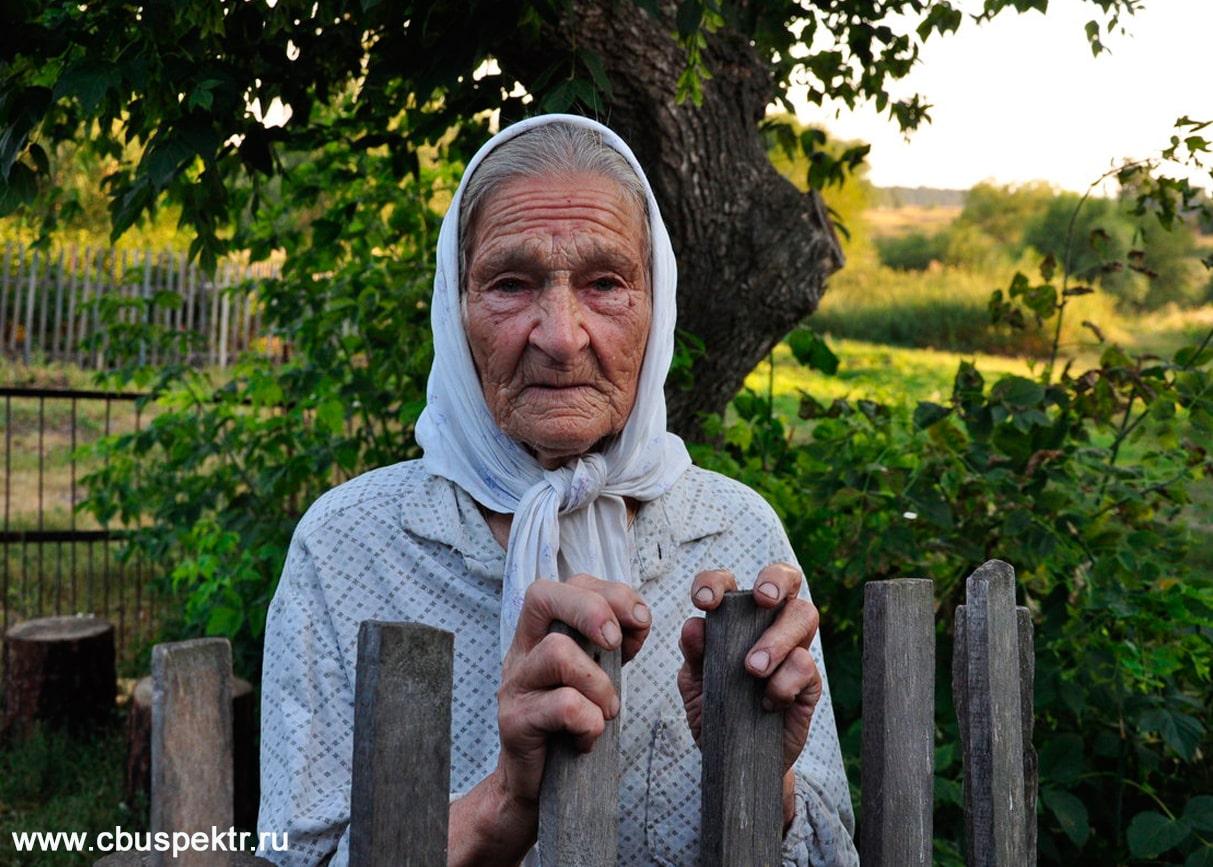 Бабушка стоит у забора