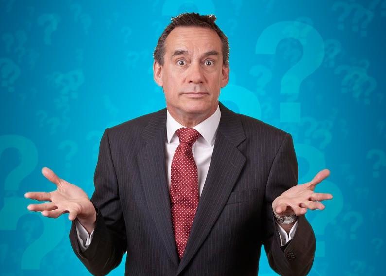 Бизнесмен разводит руками на фоне знаков вопроса