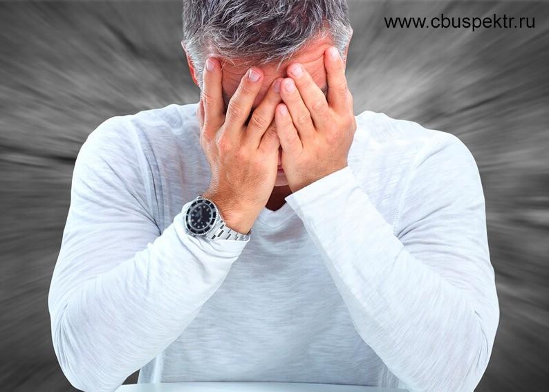 Предприниматель сидит закрыв лицо руками