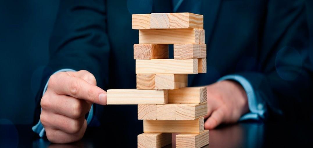 Мужчина в костюме вынимает кубик из пирамиды
