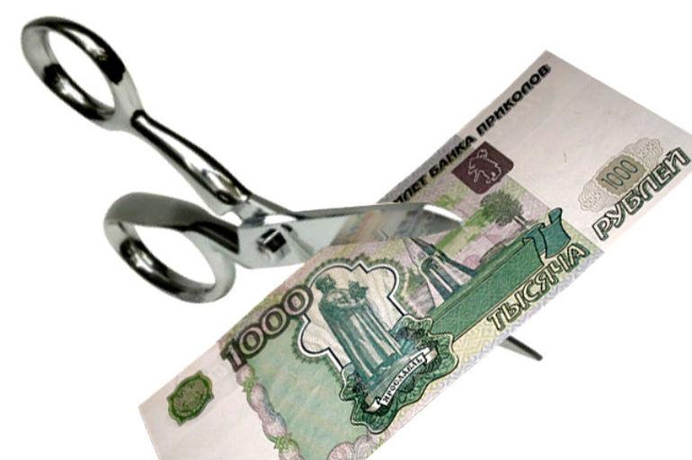 Ножницы режут тысячерублевую банкноту