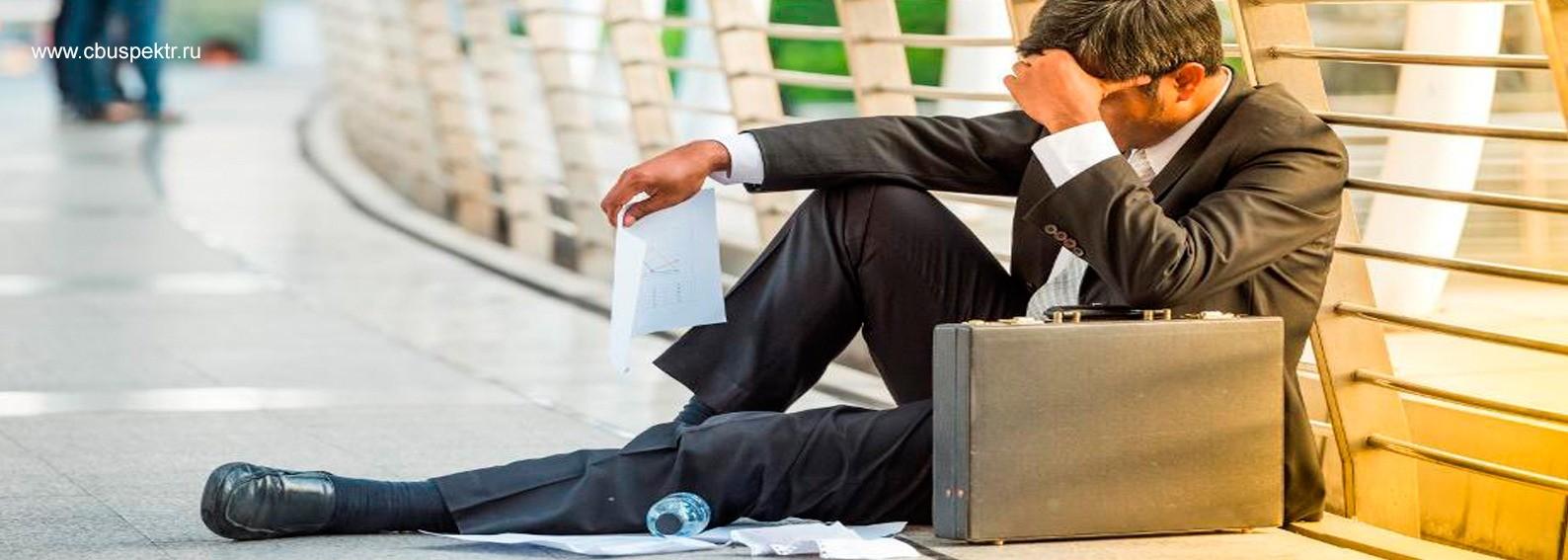 Мужчина сидит на земле уронив бумаги