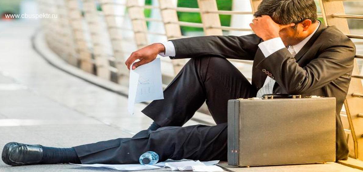 Расстроенный бизнесмен сидит схватившись за голову