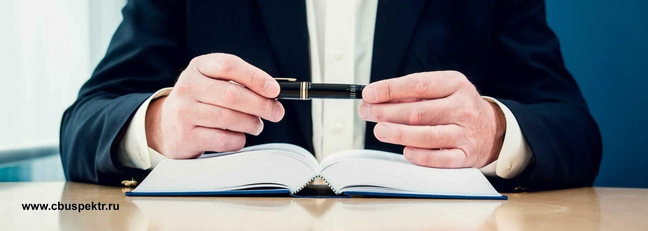 Мужчина за столом держит в руках ручку