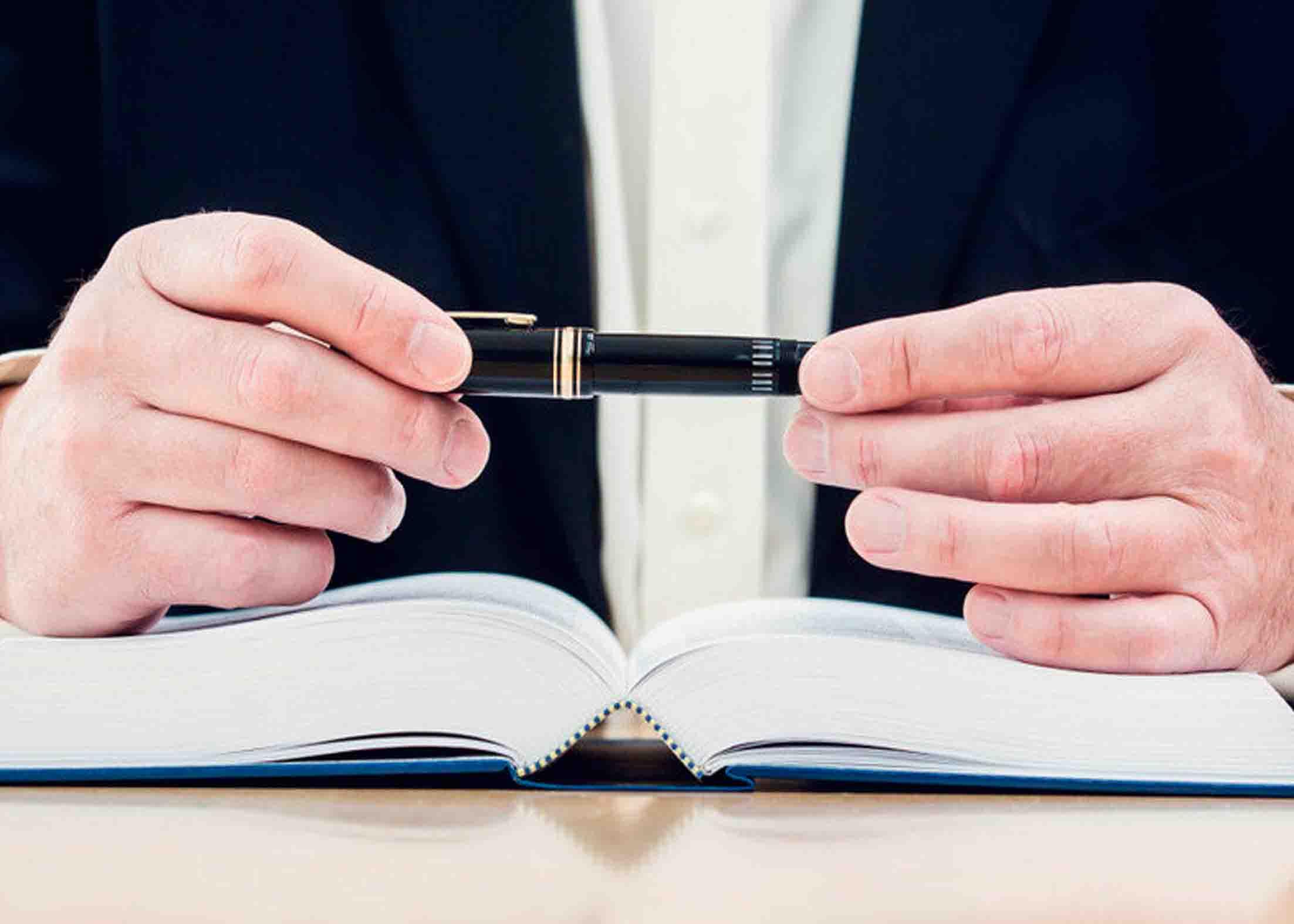 Адвокат за столом с ручкой и ежедневником