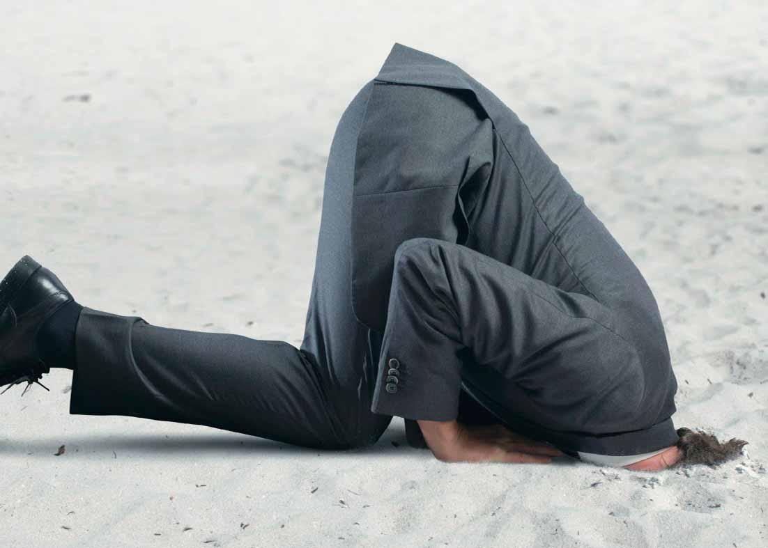 Мужчина прячет голову в песок